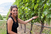 Hispanic woman looking at grapes in vineyard