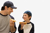 Caucasian father and son eating hot dogs