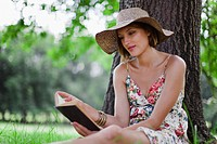 Woman reading against tree in field