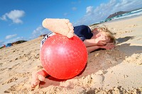 Boy playing with red ball on beach
