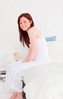 Beautiful red_haired female posing while sitting on her bed