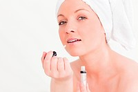 Attractive young woman wearing a towel using a lip gloss against a white background