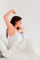 Charming brunette female posing while stretching on a bed