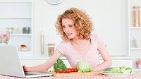 Good looking blonde woman relaxing with her laptop while cooking some vegetables in the kitchen in her appartment