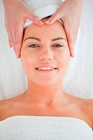 Portrait of a smiling woman enjoying a facial massage wearing a towel