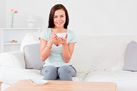 Smiling dark_haired woman drinking tea in her living room