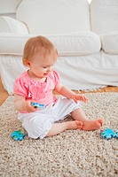 Baby playing with puzzle pieces while sitting on a carpet in the living room