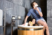 Couple in bathroom. Man shaving and woman having bath
