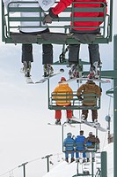 Skiers riding up lift chair