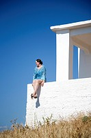 Woman with blue kaftan sitting on wall in greece