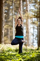 Young Woman Performing Tree Pose in Meadow of Evergreen Trees, Oswald West State Park, Oregon, USA