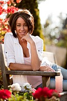 Smiling Young Woman Relaxing on Park Bench, Portrait