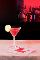Pink cocktail and L plate on bar