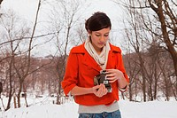 Teenage girl holding vintage camera in snow