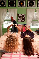 Teenage girls lying on bed with smartphones