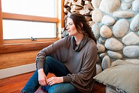 Woman sitting in log cabin, portrait (thumbnail)