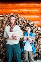 Father and son holding logs, portrait (thumbnail)