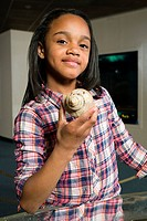 Girl holding sea shell in aquarium
