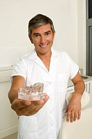 dentist holding model of human mouth, smiling