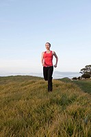Woman in workout clothes running in a field.