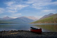 Canoe sits on lake shore in mountains