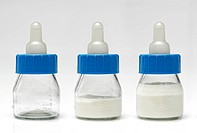 Very small feeding bottles shot on white background. These bottles are used in hospitals to feed new born babies. The bottles are placed in a row, and...