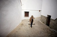 A senior man ups a hill using his walking stick in a street of El Gastor village in the Sierra de Grazalema Natural Park, Cadiz province, Andalusia, S...