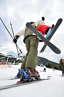 Skiers, man carrying a child. La Molina ski resort, Cerdanya, Girona province, Catalonia, Spain