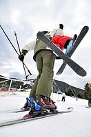 Skiers, man carrying a child. La Molina ski resort, Cerdanya, Girona province, Catalonia, Spain