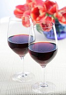 Two glasses of red wine, tulips in a glass vase