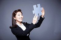 woman holding puzzle piece