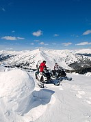 Friends stop for a break and take in the view while snowmobiling on a beautiful late winter day, Monashee mountain range, near Valemount, Thompson Oka...