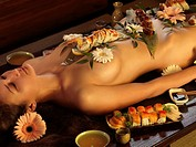 Beautiful nude asian woman lying naked on the table with sushi rolls and flowers on her naked body  Japanese Nyotaimori