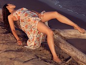 Young woman in wet summer dress lying on a driftwood on a shore during sunset
