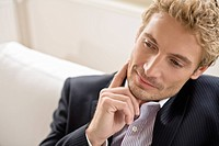 Businessman sitting with hand on chin, contemplating