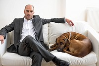 Businessman sitting on sofa with dog, portrait