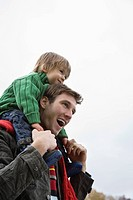 Father carrying son on shoulders, side view, low angle view