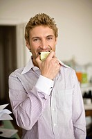 Mid adult man eating green apple, portrait