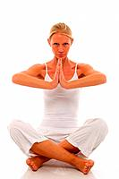 a young caucasian woman dressed in white sitting cross_legged doing yoga