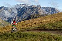 Italy, Livigno, View of woman riding mountain bike uphill