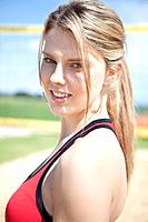 Germany, Bavaria, Mauern, Close up of young woman standing in front of beach volleyball net, smiling, portrait