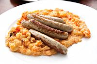 Germany, Close up of roasted sausages on top of carrot stew