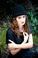 Portrait of a 19 year old brunette woman wearing a hat in a garden setting.