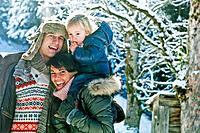 Austria, Salzburg Country, Flachau, Family standing in snow, smiling
