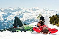 Austria, Salzburg Country, Altenmarkt_Zauchensee, Mid adult couple lying on snow in winter