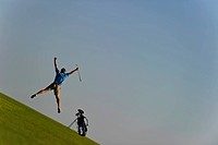 A golfer leaps into the air in celebration