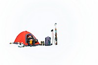 A mountaineering women sits in her tent on a snow covered mountain