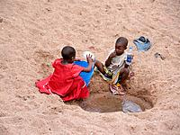 Children collecting water from a dried up river bed near Shinyanga, Tanzania