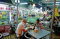 Tourists eating food at night market, Pattaya beach resort, Thailand