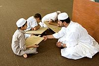 Zliten, Libya  Boys Write Verses from the Koran on their Prayer Boards in the Madrasa of Sidi Abdusalaam  Their teacher, or muqri, supervises  He wear...